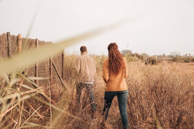 Back view couple walking through wheat field