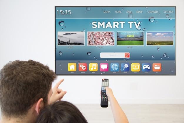 自宅のテレビでスマートテレビを見ている背面図のカップル。