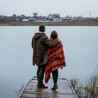 Back view of couple with blanket outdoors admiring the lake view