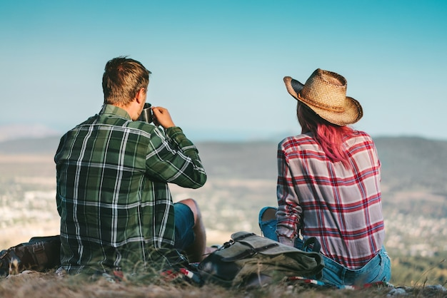 Back view of a couple of young happy backpackers having rest after achieving mountaing top, sitting on a blanket, drinking tea from a thermos-bottle and enjoying beautiful scenery of valley view.