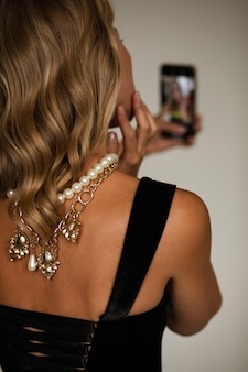 Back view crop stock photo of anonymous fair-haired lady in black top and necklaces on her back taking self-portrait
