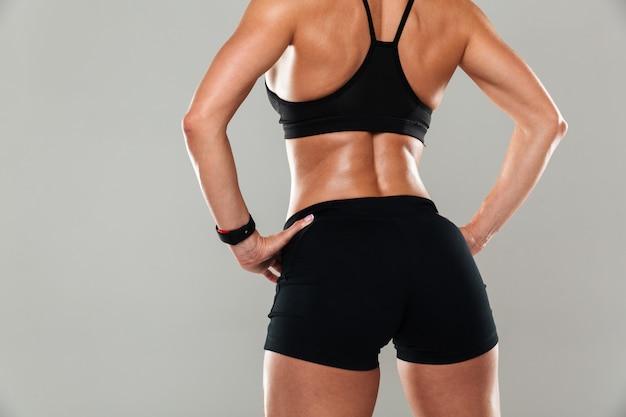 Вид сзади обрезанного изображения здоровой мускулистой женщины