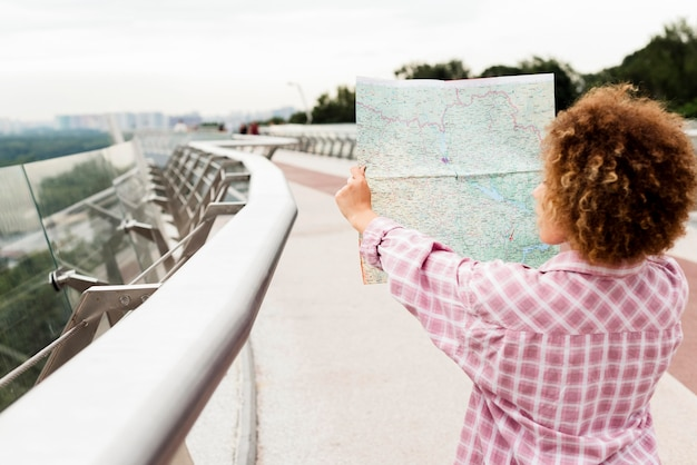 Back view curly woman checking a map