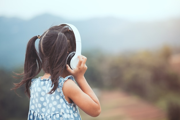Back view of cute asian child girl having fun to listen the music in headphones