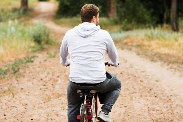 Вид сзади велосипедист на лесной дороге