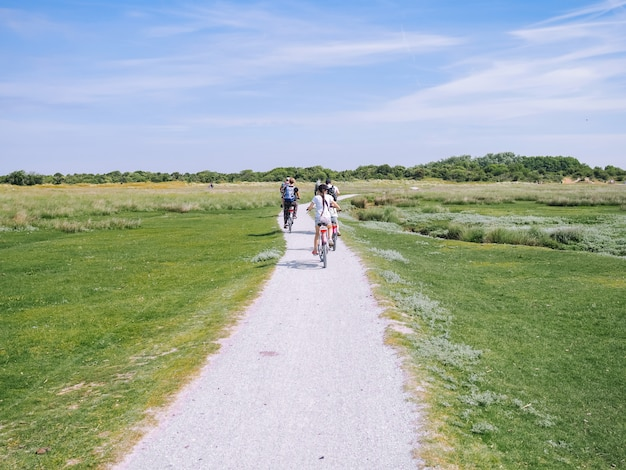 Back view cyclists family traveling on the road in the dune area of schiermonnikoog island.