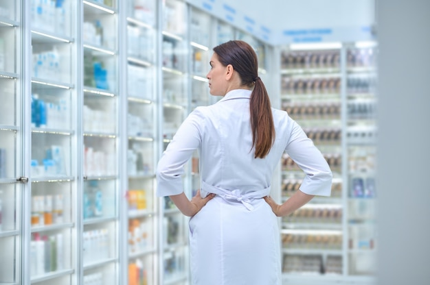 Back view of a dark-haired caucasian female druggist standing alone before the drugstore display cabinet