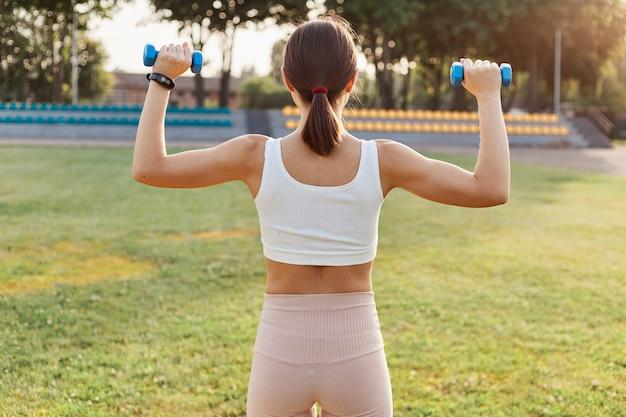 Vista posteriore della femmina dai capelli scuri con corpo sportivo che tiene manubri e fa esercizi allo stadio, allenamento bicipiti e tricipiti, attività all'aperto, stile di vita sano.