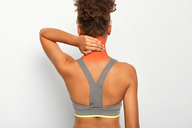 Back view of dark skinned curly woman touches neck, feels pain, needs massage, suffers from muscle injury, wears grey top, isolated on white wall