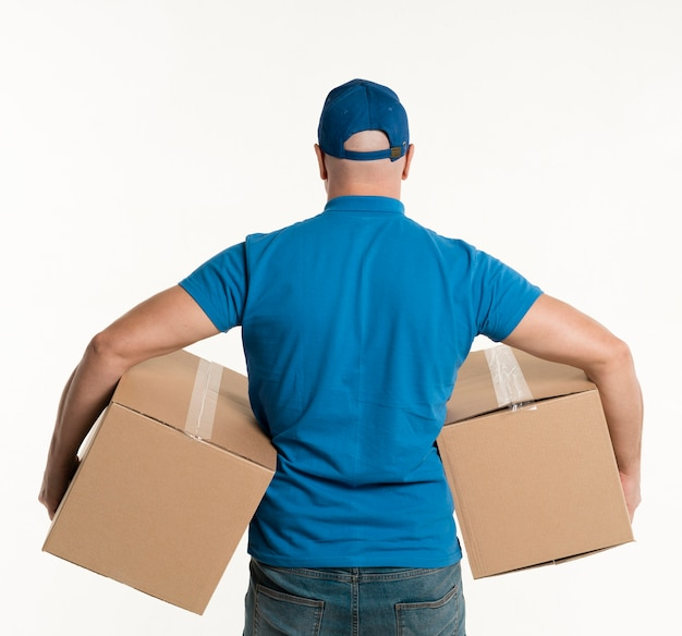 Back view of delivery man holding cardboard boxes