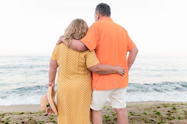 Back view of elder tourist couple