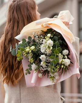 Back view of elegant woman holding bouquet of flowers outside