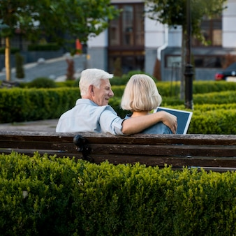 Back view of embraced older couple outdoors on bench with tablet