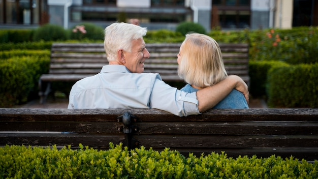 Back view of embraced older couple outdoors on bench