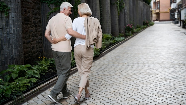Back view of embraced senior couple taking a walk outdoors