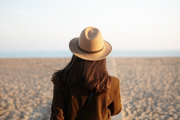 Back view of european woman in hat and coat going towards sea on boardwalk in fresh spring evening, feeling lonely