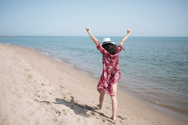 Back view excited woman walking at seashore