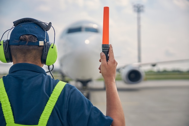 Back view of an experienced aircraft marshaller making the signal to the crew of the landed plane