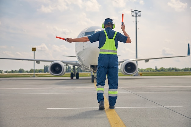Back view of an experienced aircraft marshaller making the turn right signal to the airplane