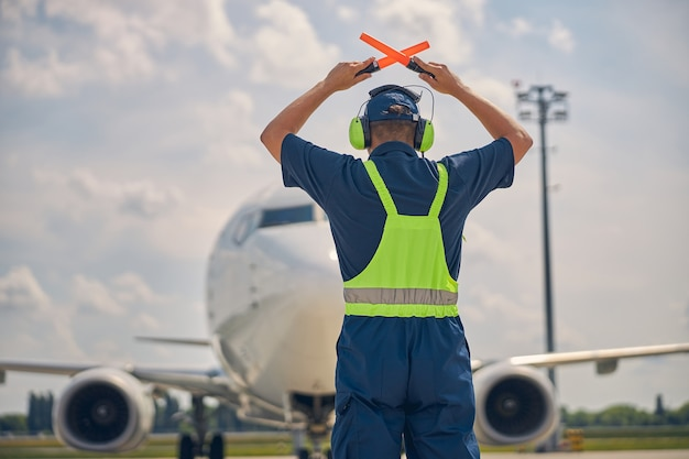 Back view of an experienced ground marshaller making the stop signal to the cockpit crew