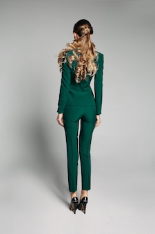 Back view of faceless blonde woman with hairstyle wearing skinny trousers and green jackets with heels over white background.