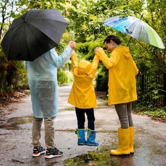 Vista posteriore famiglia divertendosi mentre piove