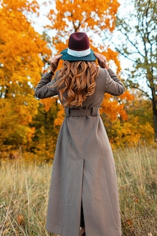 Back view of a fashionable young woman in a stylish long coat in an elegant hat with a trendy hairstyle in an autumn park among trees with orange foliage. modern girl walks through the woods.