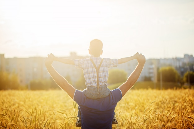 Back view of a father with his son on the shoulders standing in a field and city on summer sunset
