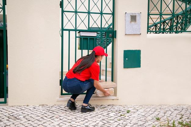 Vista posteriore del corriere femminile che mette i pacchi vicino al cancello. deliverywoman bruna dai capelli lunghi in uniforme rossa accovacciata e consegna ordine espresso al cliente a casa. servizio di consegna e concetto di posta