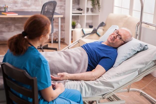 요양원에서 침대에 누워 있는 노인 옆에 앉아 있는 여성 의사를 다시 봅니다.