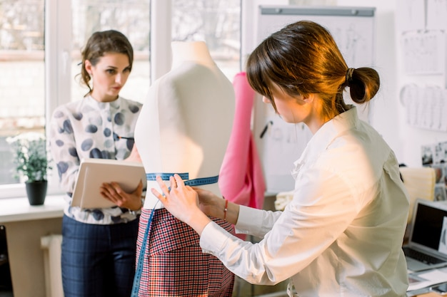 Back view of female dressmaker measuring mannequin with tape in atelier office. talented fashion shop owner designer working with sketches for new collection of clothes. dressmaking and sewing concept