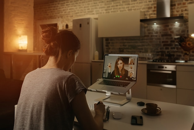 Back view of a female employee who is working remotely and doing notes during a video conference on a laptop from home.