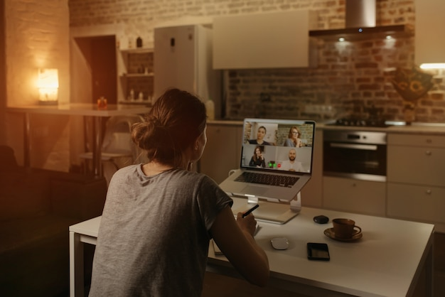 Back view of a female employee who is working remotely talking to her colleagues in a video conference on a laptop from home.