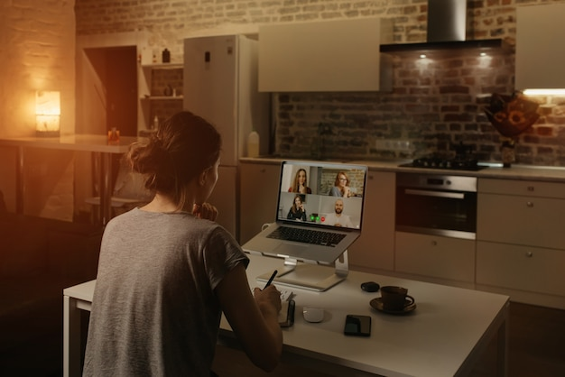 Back view of a female employee who is working remotely and talking to her colleagues in a video conference on a laptop from home.