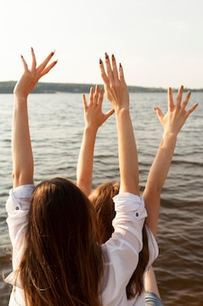 Back view of female friends at the lake with arms up