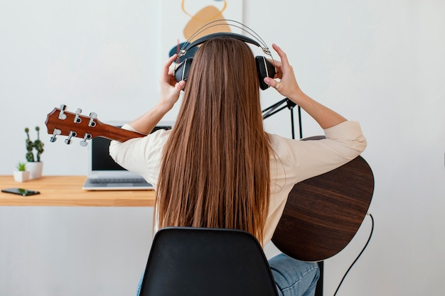Back view of female musicianputting on headphones to record song and play acoustic guitar