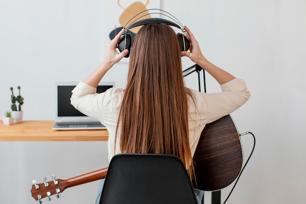 Back view of female musician with acoustic guitar and headphones