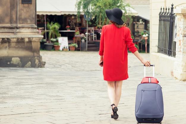 Вид сзади девушки тянет чемодан на улице города.