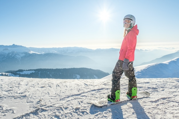 Back view of female snowboarder standing with snowboard and enjoying mountain landscape