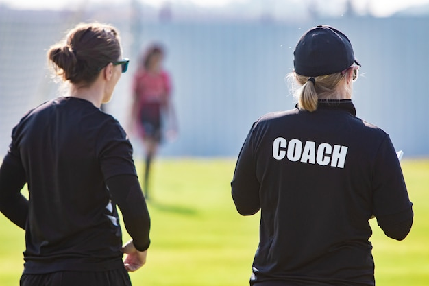 Back view of female sport coach and her assistant in black coach shirt