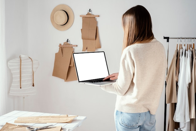 Back view of female tailor in the studio using laptop
