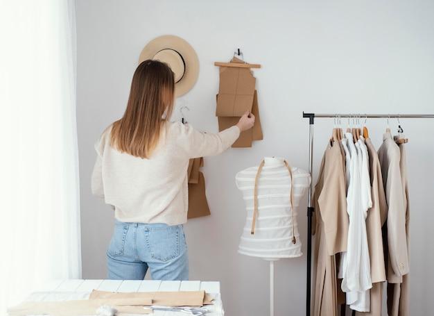Vista posteriore del sarto femminile in studio con i vestiti