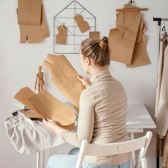Vista posteriore del sarto femminile che lavora sui modelli in studio