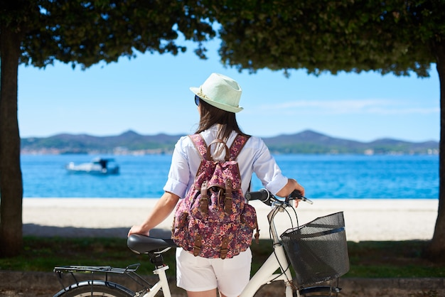 Вид сзади женский турист, стоя с велосипедом на тротуаре возле побережья под деревьями и горами