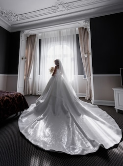 Back view of fiancee, wearing in plume wedding dress,  standing among empty room and  holding bouquet