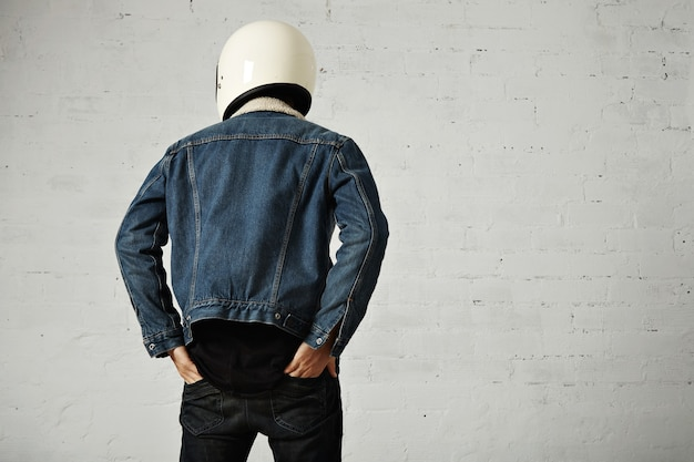 Back view on fit body of younf motocyclist wears helmet, black longsleeve henley shirt and club denim jacket with his hands in back pockets of his trousers