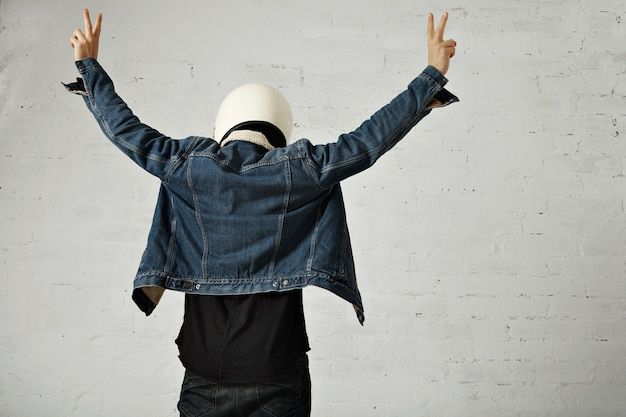 Back view on fit body of younf motocyclist wears helmet, black longsleeve henley shirt and club denim jacket with his hands up showing peace gesture