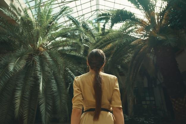 Вид сзади подходит экзотическая женщина, наблюдающая за пальмами в тропическом саду