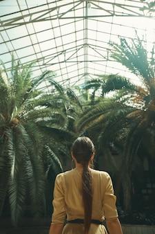 Вид сзади подходит экзотическая женщина, наблюдая за пальмами в тропическом саду