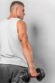 Vista posteriore dell'uomo in forma che tiene il peso con lo spazio della copia